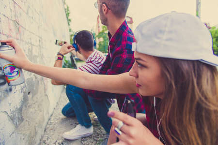 One friend is taking pictures of his two friends who are doing graphites on the wall