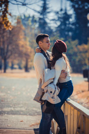 Amorous couple is hugging on the bridge in the park and enjoying the beautiful autumn day