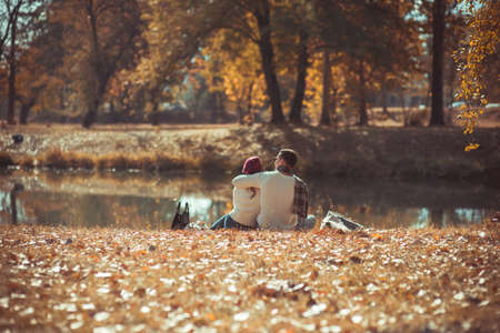Romantic couple is sitting by the river in the park and spending quality time together