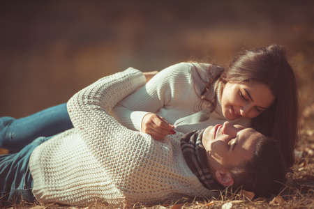 Charming couple is spending carefree time in the park, lying on the grass and resting