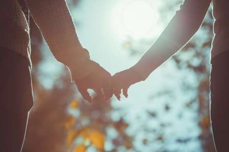 Attractive, beautiful  couple is holding hands outdoors on a sunny day Banco de Imagens
