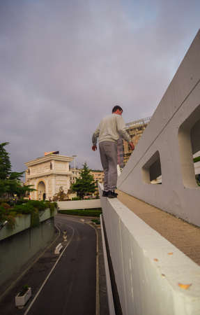 Sporty man train parkour while standing on the edge on the high wall Imagens
