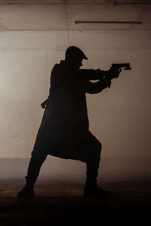 A man is standing in a dark room and holding pistol in his hands Stock Photo