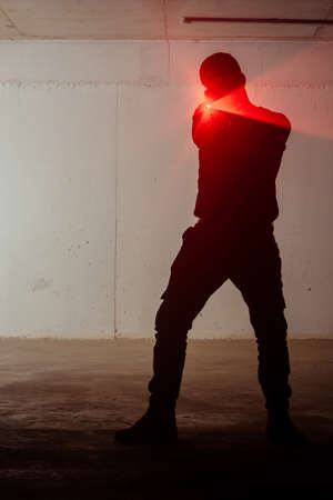 A man is standing in a dark room and holding laser gun in his hands