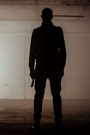 Silhouette of a man standing still with a revolver in his hands 写真素材 - 114533307