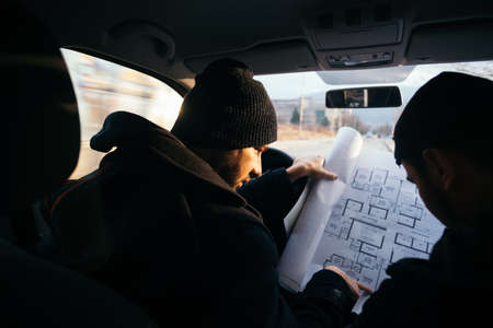Two violent robbers sitting in a car looking at a blueprint of the building they want to rob while proudly showing off their guns.