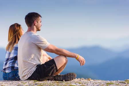 Bewundern Sie die Aussicht von der Spitze der Welt. Ein Paar, das die Sonne und den Blick auf einen Gipfel des Berges genießt und einen Zen-Moment hat, Klippe bei Sonnenuntergang. Erfolg, Gewinner, Zen, Ruhe, Meditation.