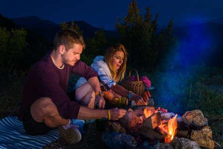 Homme et femme rôtissant des saucisses sur le feu de camp, buvant de la bière et se relaxant près du feu de camp au sommet de la montagne pendant la nuit. Concept de feu de camp romantique.