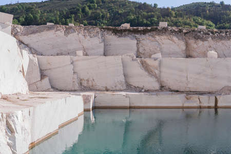 Marble quarry landscape in the mountains with a turquoise lake water