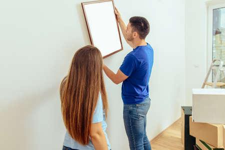 Glückliches Paar, das zu Hause ein Bild an der Wand hängt