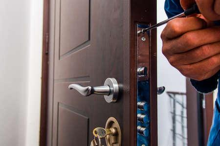 El artesano está de pie y mirando en la puerta marrón.