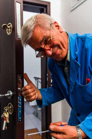 El cerrajero está de pie en el pasillo y está arreglando la cerradura de la puerta. Foto de archivo