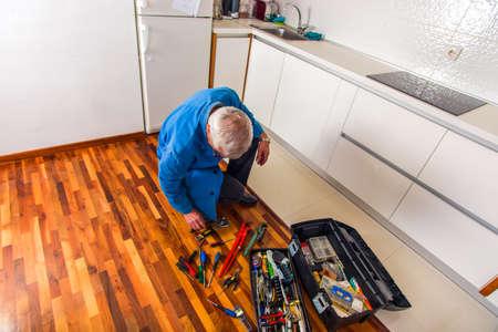Senior handyman standing next to his tool box Stock Photo