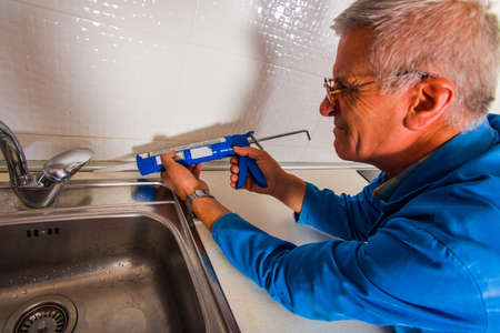 Handyman is holding caulking gun and fixing the basin in the kitchen