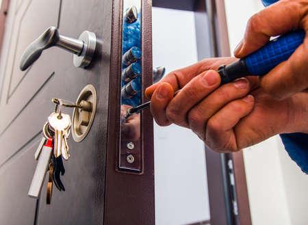 El reparador está de pie en el pasillo y fija la cerradura de la puerta con un destornillador