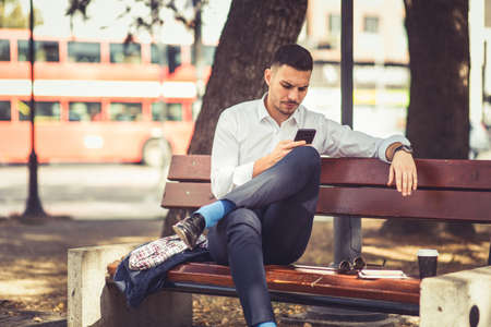 Modern businessman is sitting on a bench in the park and he is looking at his phone, behind him there is a road and double-decker bus Imagens