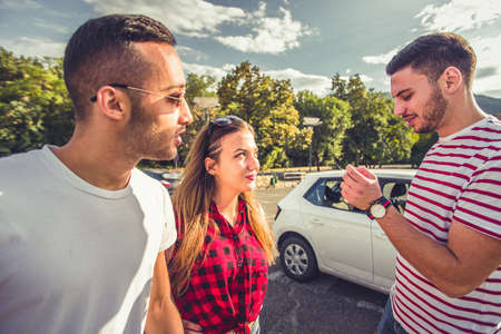 Two guys and a girl are talking while standing on parking near car