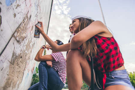 Young and careless friends spending time together and writing letters on wall with spray
