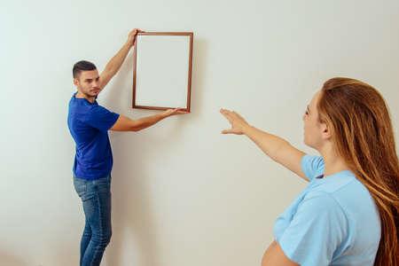 Glückliche junge Familie, die Platz für Bild im Wohnzimmer zu Hause wählt Standard-Bild