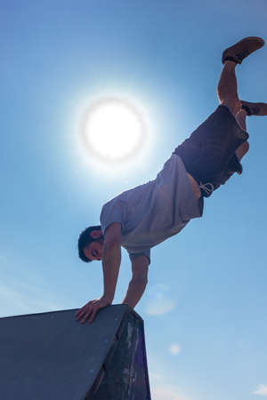 Parkour man doing handstand on pyramid in skatepark