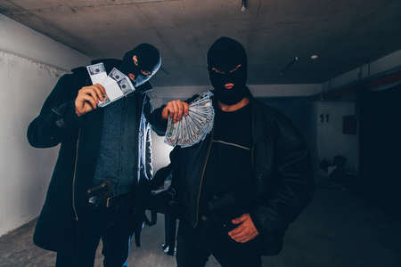 Robbers with masks are standing and holding stolen money in hands