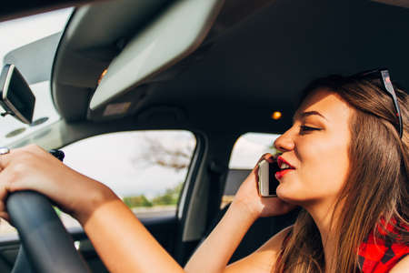 Young woman worried and stressed driving car while talking with mobile phone distracted in risk, reckless driving Imagens