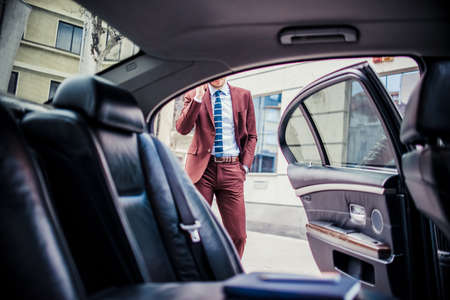 Reicher Geschäftsmann, der beim Telefonieren auf dem Handy steht, um das Auto zu öffnen