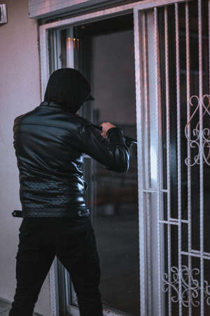 Hooded housebreaker forcing window lock to make a theft in a house Stock Photo