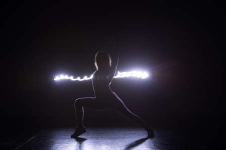 Modern art dancer, dancing in front of a black background with neon blue light while steching and twisting her body.