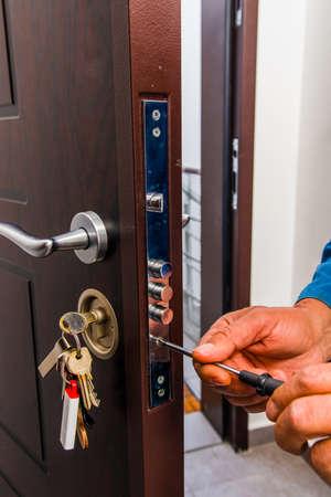 Slotenmaker repareert de deur met een schroevendraaier