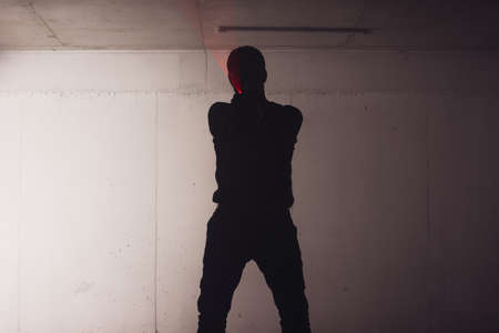 silhouette of an armed man holding his gun and pointing with his laser beam at a target. Stock Photo