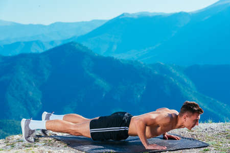 Handsome athlete ( sportsman ) doing push ups on top of a mountant whit an amazing view on the landscape. Stock fotó