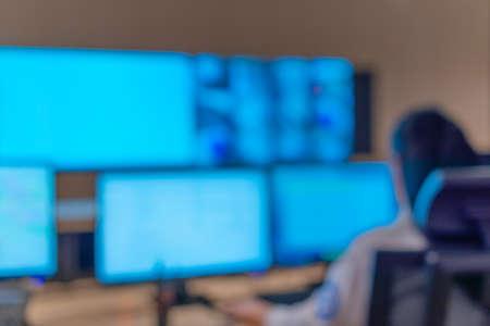 Photo floue d'agents de sécurité travaillant sur des ordinateurs alors qu'ils étaient assis dans la salle de contrôle principale