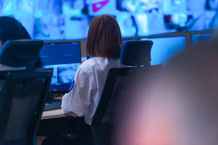 In the System Control Room, Technical Operator Works at His Workstation with Multiple Displays, Security guard working on multiple monitors. Stock Photo