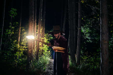 Young guy wearing halloween wizard costume and performing spells in the middle of dark woods