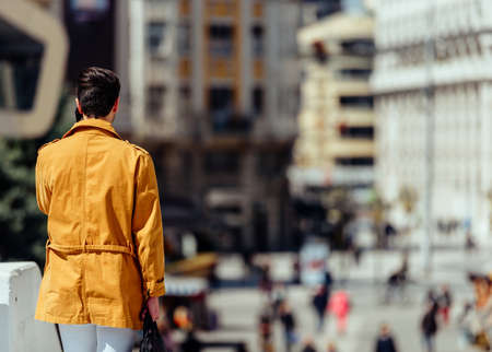 Businessman in yellow coat waking down the square