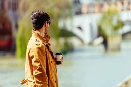 Man holding coffee to go while standing next to the river in down town