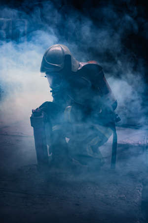Portrait of a female firefighter wearing a helmet and all safety equipment a while holding a tomahawk and wearing an oxygen mask indoors surrounded by smoke