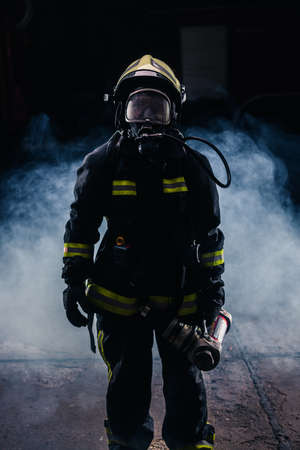 Portrait of a female firefighter wearing a helmet and all safety equipment a while holding a tomahawk and wearing an oxygen mask indoors surrounded by smoke Foto de archivo