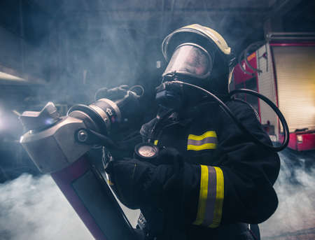 Portrait of a female firefighter wearing a helmet and all safety equipment a while holding a tomahawk and wearing an oxygen mask indoors surrounded by smoke Archivio Fotografico