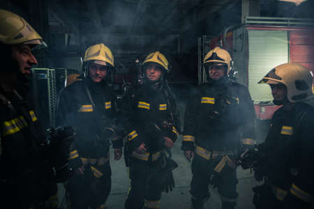 Team of firefighters standing inside ( indoors ) a buliding next to a fire engine.