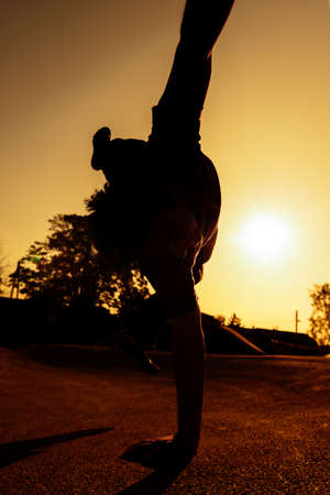Acrobatic silhouette man exersicing parkour and gymnastic moves at a skatepark