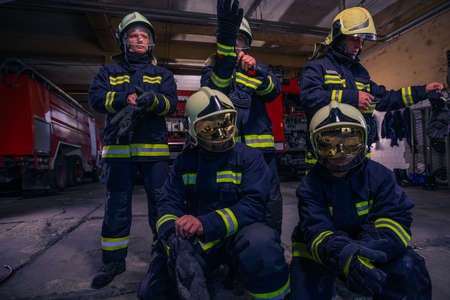 Portrait of group firefighters in front of firetruck inside the fire station
