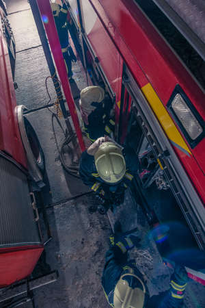 Firemen checking the fire engine inside the fire department from a bird perspective Stockfoto