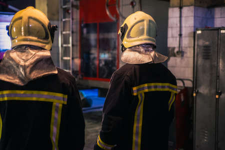 Two young men wearing helmets posing from the back inside the fire station.