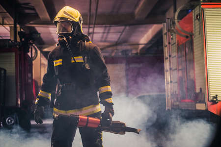 Portrait of young fireman standing and holding a chainsaw in the middle of the chainsaw's smoke