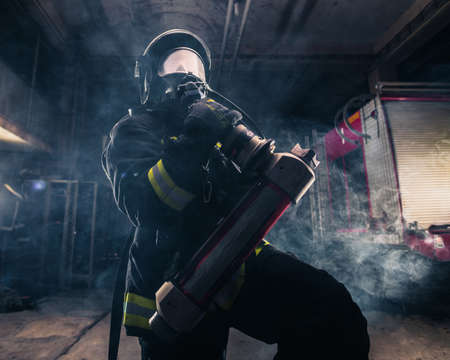 Portrait of a female firefighter wearing a helmet and all safety equipment a while holding a tomahawk and wearing an oxygen mask indoors surrounded by smoke Reklamní fotografie