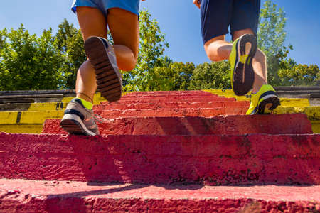 Fitness couple with muscular legs running through stairs Zdjęcie Seryjne