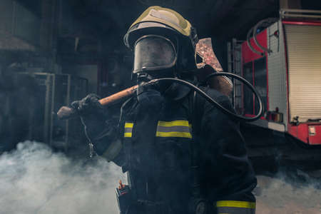Portrait of a fireman wearing firefighter turnouts holding a rescue axe. Dark background with smoke and blue light. Stockfoto