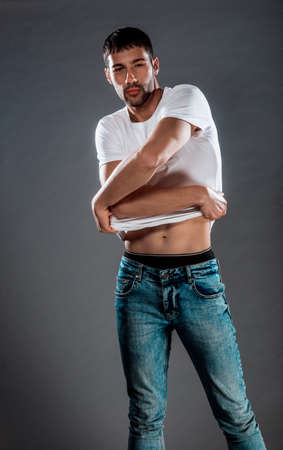 Attractive stylish man posing in blue denim pants and white top